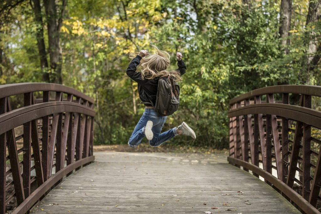 Girl jumping on bridge